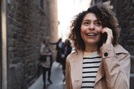 Smiling woman talking on cell phone in an alley - FMOF00490