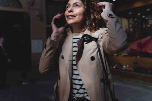 Smiling woman talking on cell phone in an alley - FMOF00493