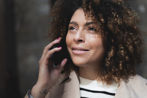Portrait of smiling woman talking on cell phone - FMOF00496