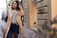 Smiling woman walking in the city - FMOF00502