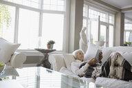 Relaxed senior woman digital tablet living room sofa - HEROF32703