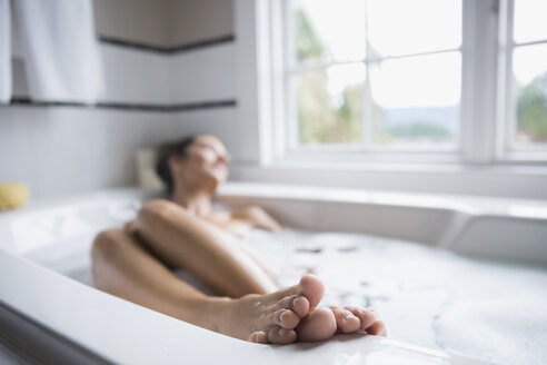 Serene woman with feet up in bubble bath - HEROF32709