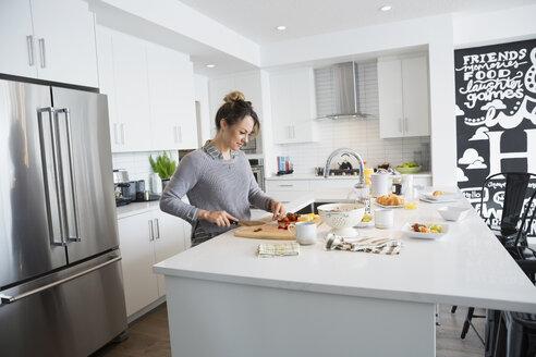 Woman cutting fruit in kitchen - HEROF32756