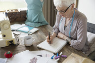 Senior woman seamstress sketching in notebook in home office - HEROF32765
