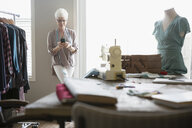 Senior woman seamstress using cell phone in home office - HEROF32771