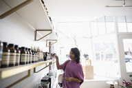 Woman shopping browsing merchandise on shelves in home fragrances shop - HEROF32783