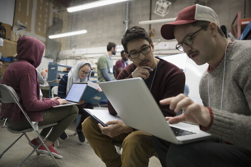 Team of hackers brainstorming using laptop at hackathon in workshop - HEROF32807