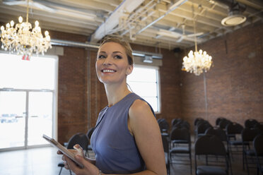 Smiling businesswoman with digital tablet in conference room with chandeliers - HEROF32816