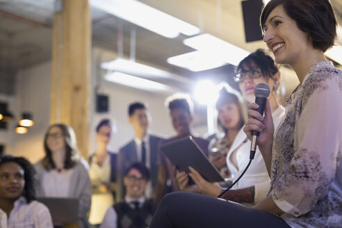 Smiling businesswoman with microphone and digital tablet leading conference meeting - HEROF32822