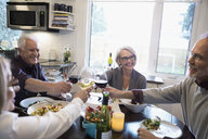 Smiling senior couple friends toasting wine glasses and eating dinner at dining table - HEROF32831
