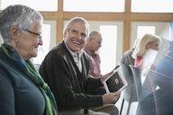 Smiling senior man student using digital tablet in classroom - HEROF32870