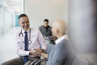 Smiling male doctor holding hands with bald female cancer patient in waiting room - HEROF32888