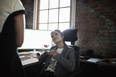 Smiling, attentive businesswoman listening to colleague in office - HEROF32931