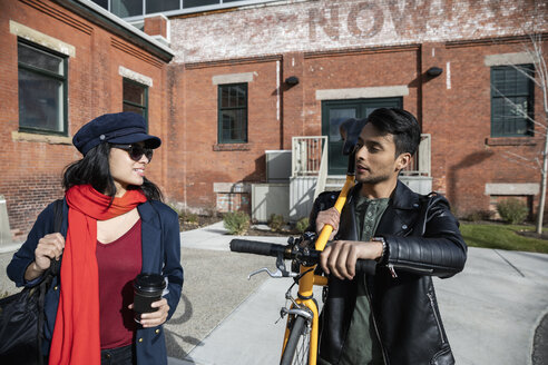 Couple with bicycle walking outside sunny brick building - HEROF32934