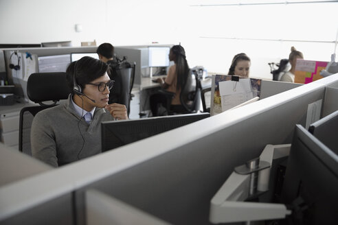 Man with headset working in cubicle at call center - HEROF32991