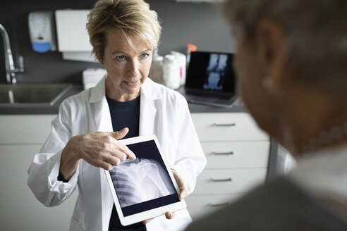 Female doctor showing patient x-ray on digital tablet in clinic examination room - HEROF33027