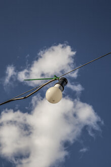 Lightbulb hanging at wire cable in front of cloudy sky - JMF00441