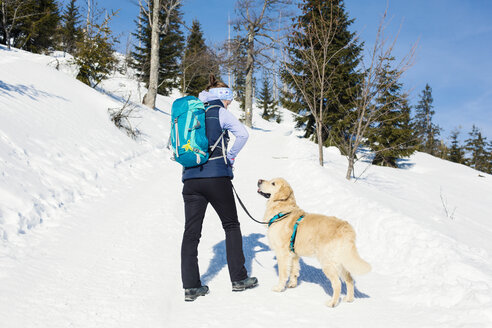 Germany, Bavarian Forest, Lusen, woman with dog hiking in winter - MAEF12829
