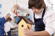 Student attaching roof to birdhouse in woodworking class - JUIF00781