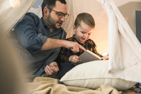 Father and son reading a book together in tent at home - UUF16856