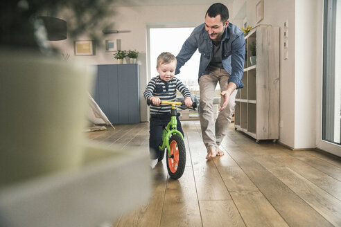 Father helping son riding with a balance bicycle at home - UUF16874