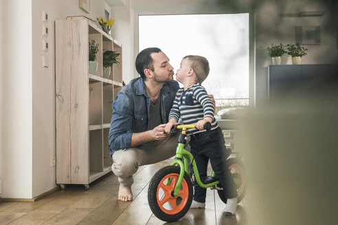 Father kissing son with a balance bicycle at home - UUF16877