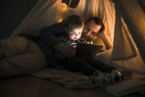 Father and son sharing a tablet in a dark tent at home - UUF16880