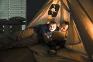 Father and son sharing a tablet in a dark tent at home - UUF16883