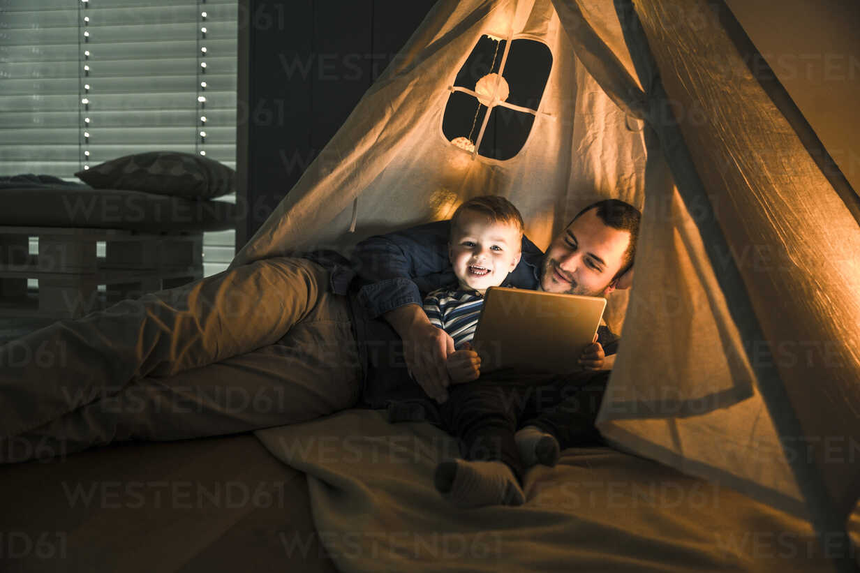 Father and son sharing a tablet in a dark tent at home - UUF16883 - Uwe Umstätter/Westend61