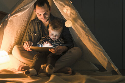 Father and son sharing a tablet in a dark tent at home - UUF16886