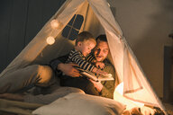 Father reading book to son at an illuminated tent at home - UUF16892