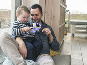 Father and son playing with a toy robot at home - UUF16904