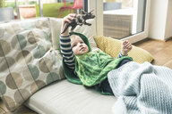 Boy in a costume lying on amattress playing with toy figure at home - UUF16916