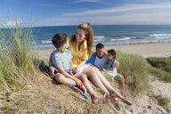 Family sitting on sunny beach - JUIF00827