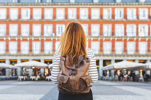 Spain, Madrid, Plaza Mayor, back view of redheaded young woman with backpack in the city - WPEF01451