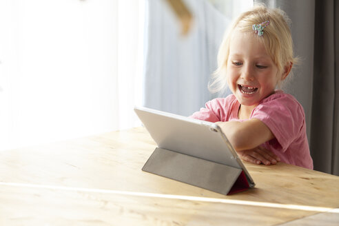 Portrait of blond little girl using digital tablet at home - GAF00099