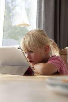 Portrait of blond little girl using digital tablet at home - GAF00102