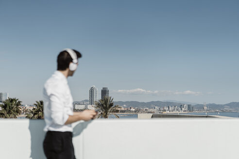 Spain, Barcelona, businessman listening music with headphones and smartphone on roof terrace looking at distance - AFVF02676