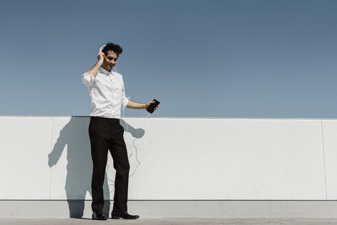 Happy businessman listening music with headphones and smartphone on roof terrace - AFVF02679
