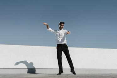 Ballet dancer with headphones practising on roof terrace - AFVF02682