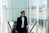 Portrait of businessman with sunglasses, coffee to go and baggage on stairs - AFVF02694
