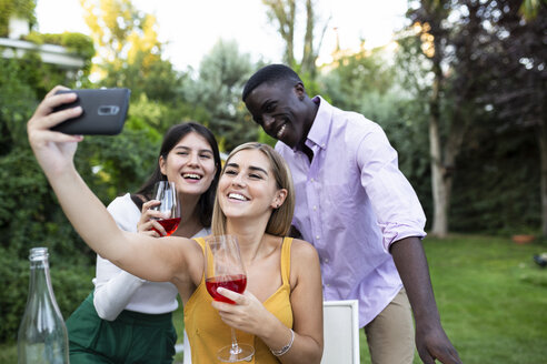 Friends having fun at a summer dinner in the garden, taking selfies - ABZF02286