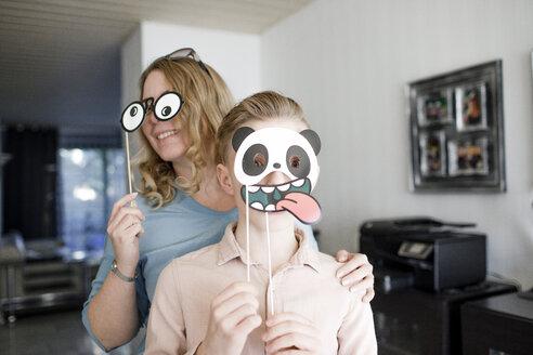 Dortmund, NRW, Deutschland. Eine lachende Frau und ein lustiger Teenager , die lustige Karneval Maske tragen, stehen in einem Wohnzimmer - KMKF00803