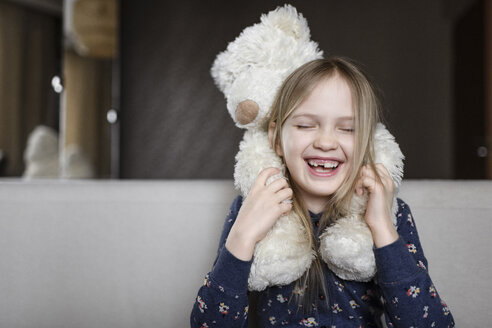 Portrait of laughing little girl with tooth gap holding white teddy bear - EYAF00078