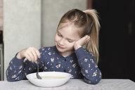 Portrait of smiling little girl eating oat meal - EYAF00084