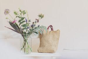 Flower vase and open calendar on white bench, linen shopping bag - MMAF00865
