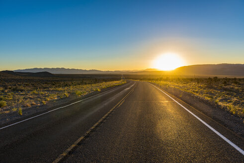USA, Nevada, Long winding road at sunset - RUNF01686