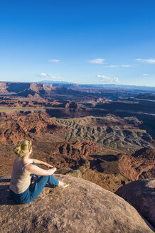 USA, Utah, Woman at a overlook over the canyonlands and the Colorado river from the Dead Horse State Park - RUNF01692
