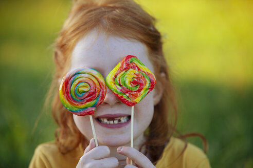 Happy girl covering her eyes with lollipops - GAF00110