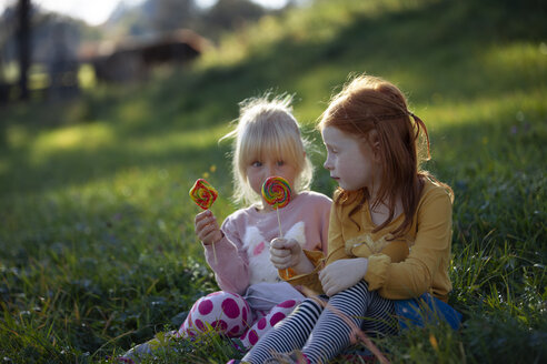 Two sisters sitting in a field holding lollipops - GAF00113